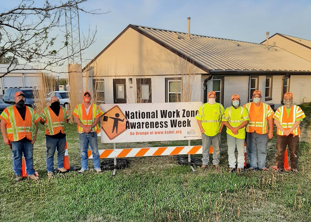 Highway personnel in front of sign